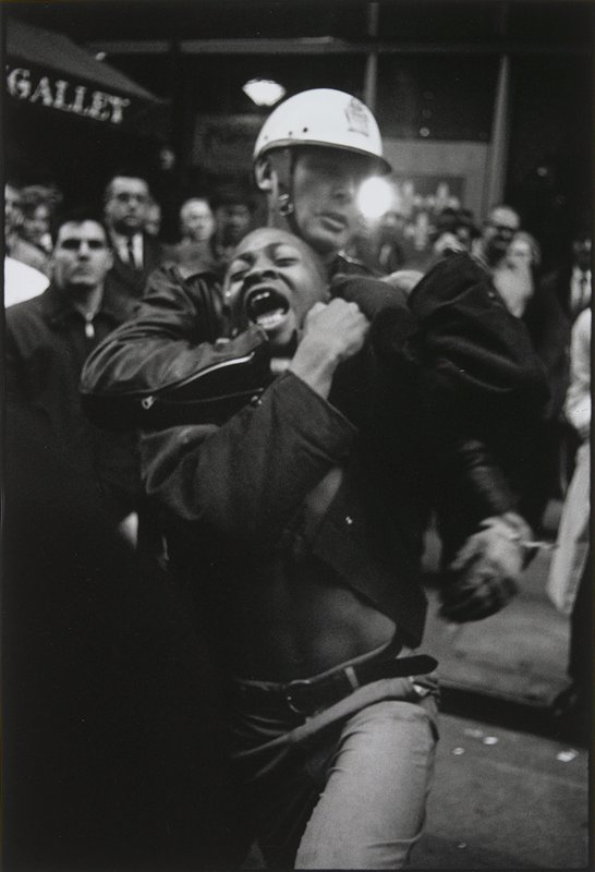 yelling, struggling black man being held in a choke-hold by a helmeted policeman; other figures in background