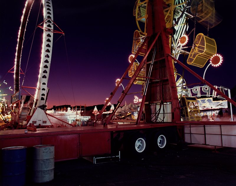 back side of ride called the Zipper; another large wheel-shaped ride at L; dark sky with pink horizon