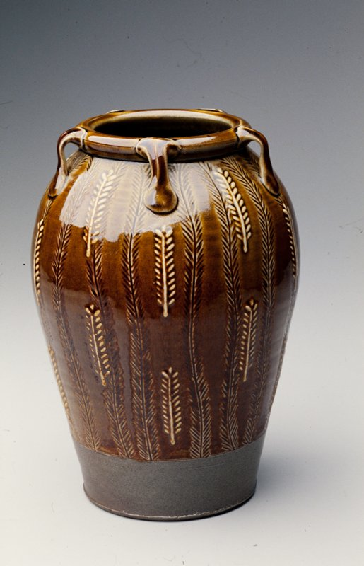 wide foot with slightly flaring shoulder; rolled lip with 5 decorative handles; applied and incised wheat sheafs overall; brown glaze