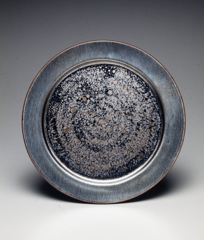 silver metallic glaze on underside and rim of top side; central glaze on top is black, silver and copper with swirls and circular drops; glazed echizen stoneware 'temmoku'
