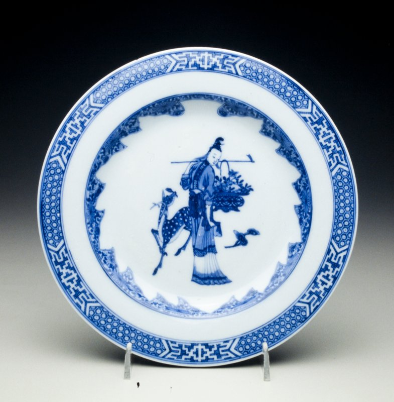 blue and white porcelain plate standing lady immortal holding basket of flowers over shoulder flanked by spotted deer and lingzhi sprays, lattice-work panelled cell-pattern border