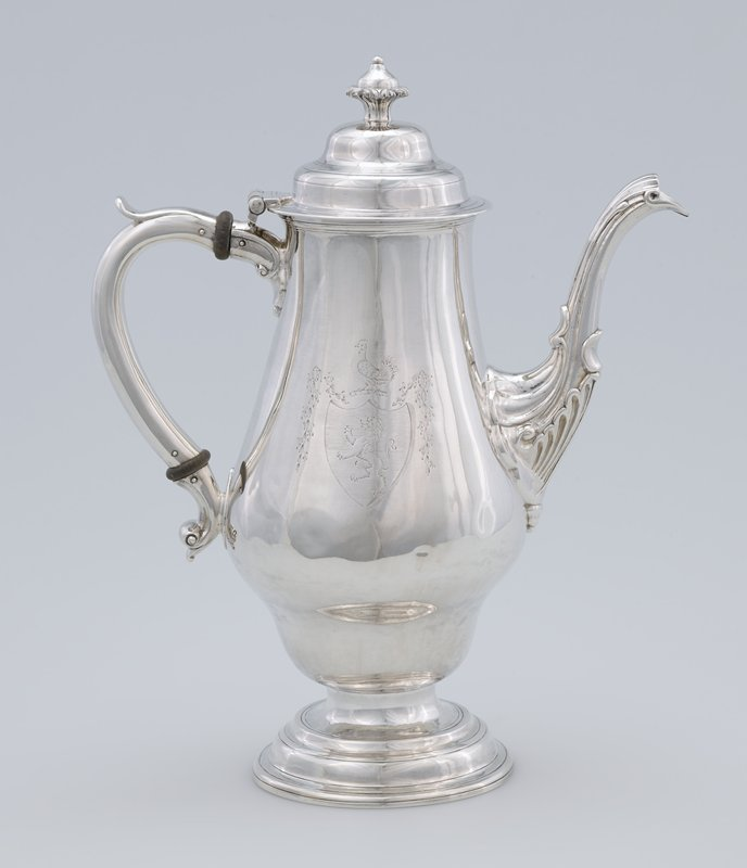 coffee pot, vase-shaped with long spout and 'S' scrolled handle; base of spout decorated with leaf motif; engraved crest on body: body engraved on one side with a crest composed of a heart-shaped shield charged with a lion Rampant, ensigned by a cock and draped with delicate sprays of flowers