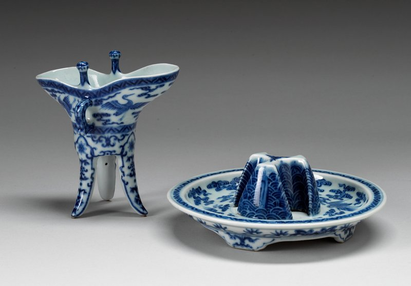 white with underglaze blue decor; Qianlong four-character seal mark and period two mushroom rim caps, loop handle and three flaring tall legs painted with band of flying cranes below rim and repeated around well of base; molded with three peaks at center to support Jue on short four-footed stand