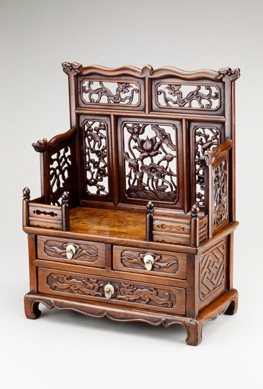 miniature high back thrown consisting of 5 carved panels on back and one on either side; Three drawers at bottom half with silver teardrop pulls, one length, two side by side