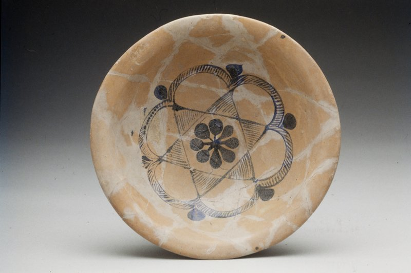 Bowl, early Islamic Samarra type, with rounded sides and slightly flattened out-turned rim. Greyish white glaze painted in darkish blue with conventional design consisting of eight-petaled opaque flower within the six-pointed median star, the whole enclosed within a six-scalloped circle. Broken and mended. Rey excavation.