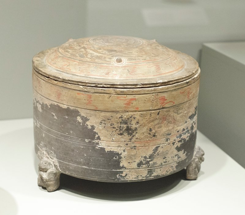 Lien (casket), circular, standing on three bears legs, black terra cotta, covered with white slip; painted in red and black design of dragons and clouds. These hill jars usually decorated with bands of relief instead of painting. Examples of Han painting are rare.