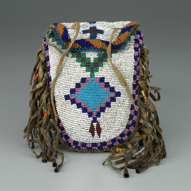 small pouch with flap at top, rounded bottom; fringe at sides with metal cone beads and porcupine quills; beaded overall with geometric designs
