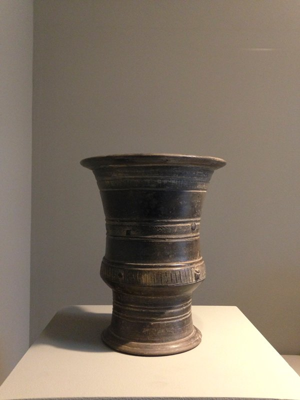 Jar, round, with decoration of incised geometrical designs in three bands around shoulder and body. Three projecting rings for handles- two on shoulder and one midway between on lower part of body; polished surface, no glaze. Grey earthenware.