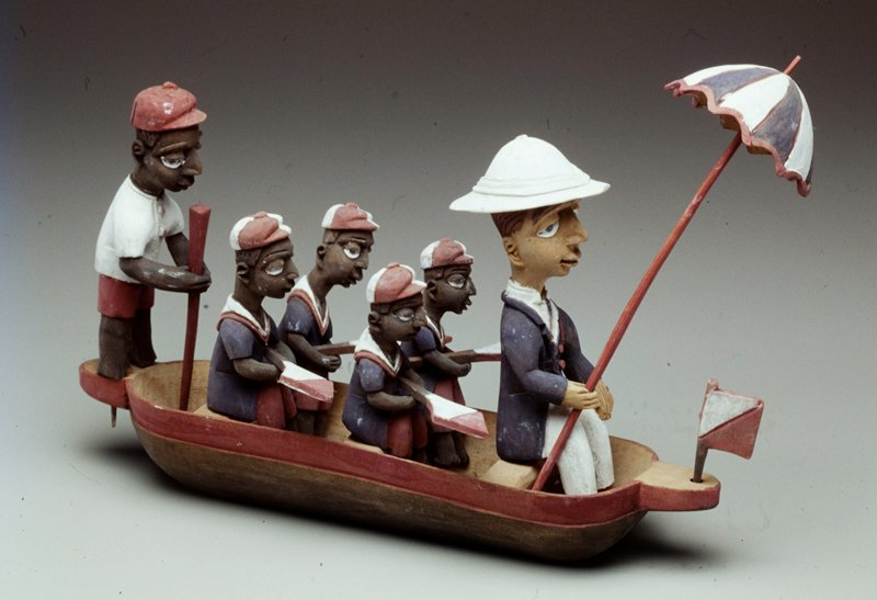 the European wearing solar topi, an umbrella in his right hand sits in front of four native oarsmen wearing caps and holding paddles; a standing native at the stern of the boat