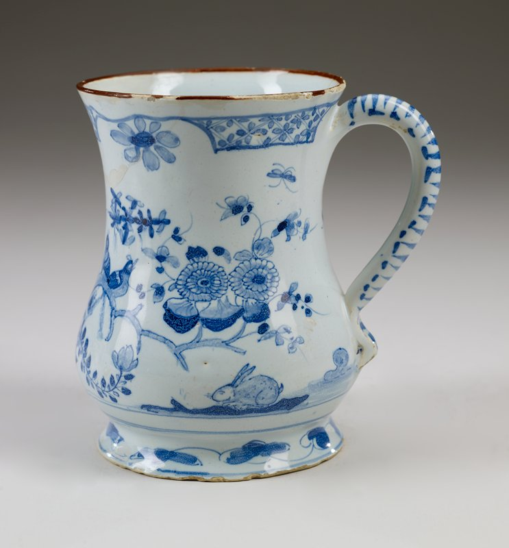 ceramic mug with handle and flaired foot; blue and white organic motif, two birds sitting together on a tree branch