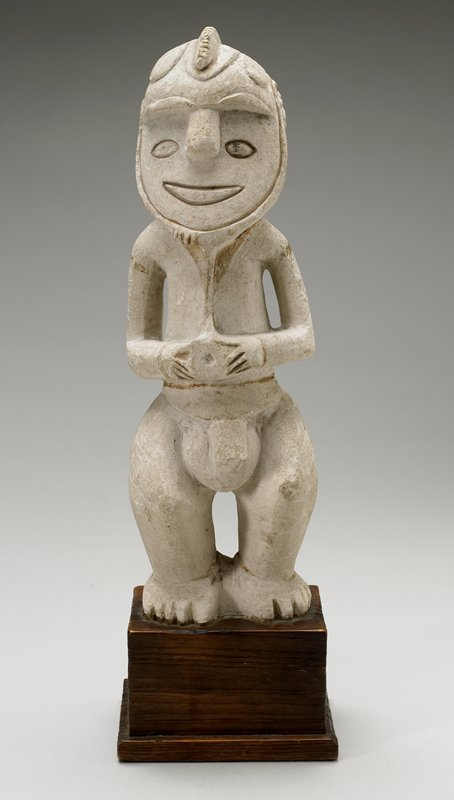 standing male figure with slightly bent, arms bent at sides; holding implement at navel, face with incised mouth and eyes, prominent nose, overhanging brow with serrated median crest