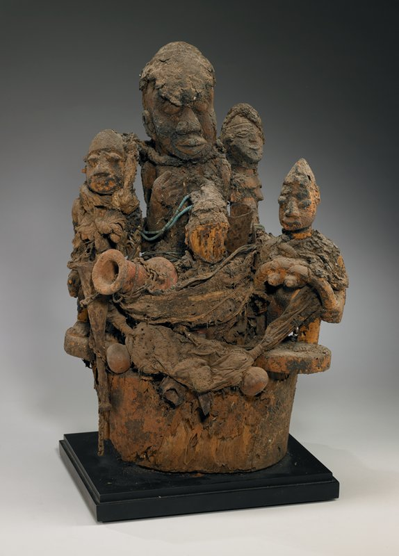tallest figure in center, with 3 other smaller figures surrounding it; possible 4th figure in front; 2 metal bells and small terra cotta vessels tucked between figures and cloth wraps