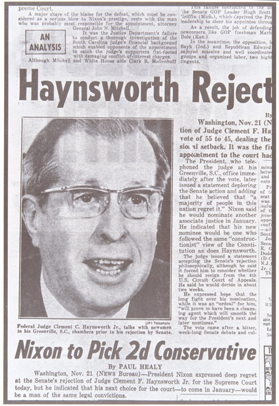 newspaper photograph of a man wearing glasses