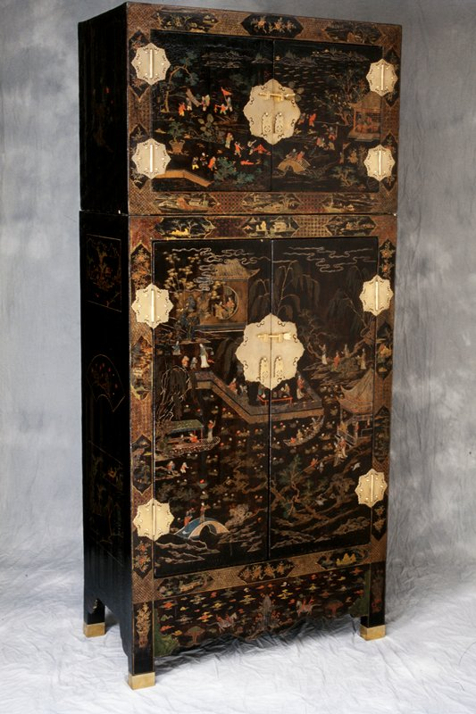 upright rectangular cupboard; two sections, upper removable hat box; two doors each with surface mounted pierced foliate hinges and lock plates, two lock pins with floral finials; upper and lower doors have continuous landscape designs in color on black ground