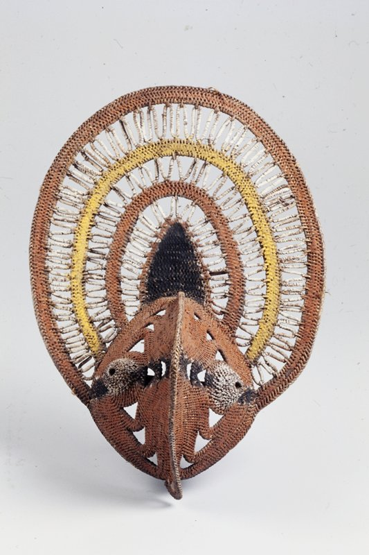 pointed face with bulging white eyes; ovoid headdress with radiating design of alternating linear zigzags and solid color bands or rust red and yellow; wooden pick behind supports face