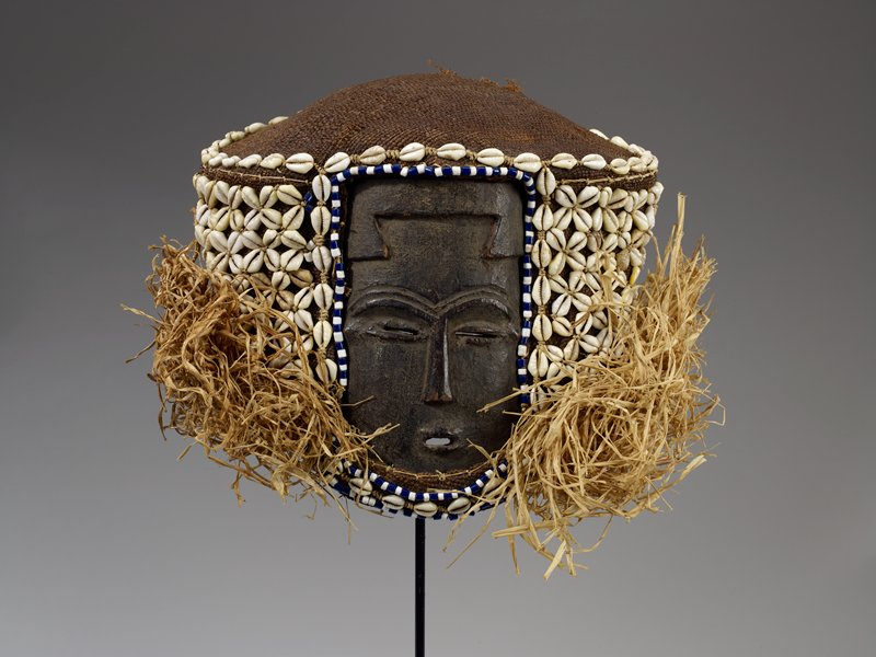 small, flat face with flat nose, slit eyes and small open mouth; large cloth head covering decorated with shells and beads; loose raffia strands on sides and back