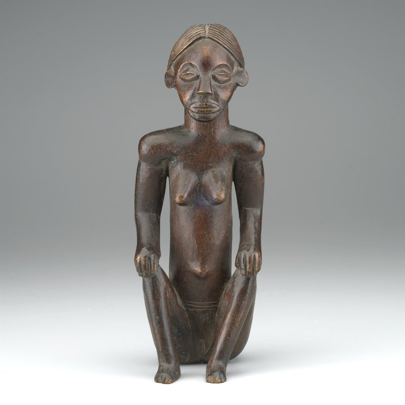 seated female figure with back very straight; knees apart and feet flat on the ground; hands on knees; long face