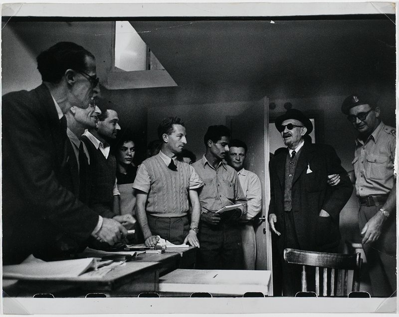 black and white photograph of group of men around ballot box