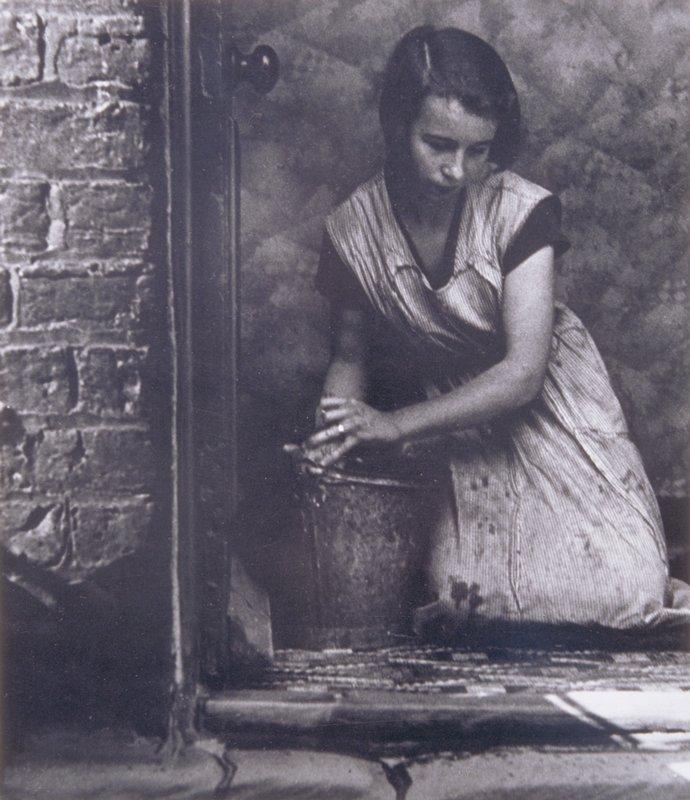 kneeling woman leaning over a bucket, cleaning a floor, seen through an open door