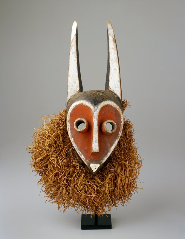 red face, white nose and mouth and long horns on top of head; raffia around sides of head and chin