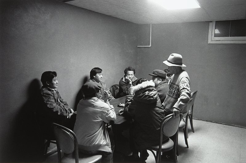 black and white photo of eight Hmong men seated around table