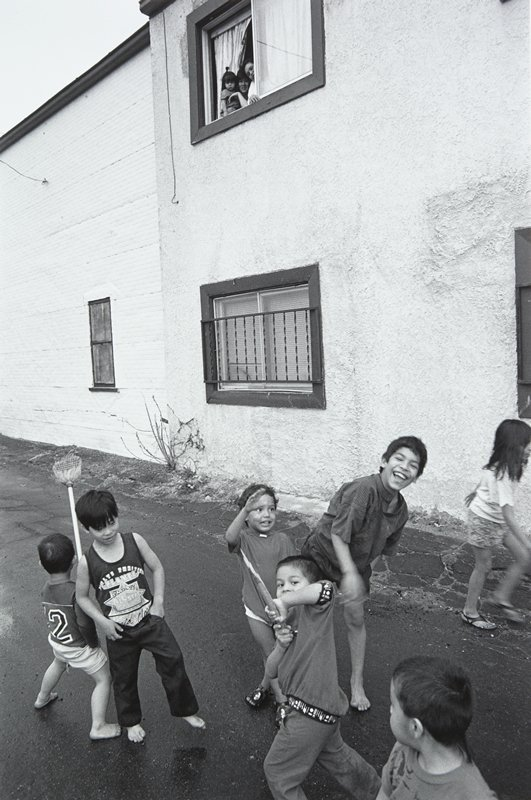 black and white photo of house with three children in window, seven children playing in street below
