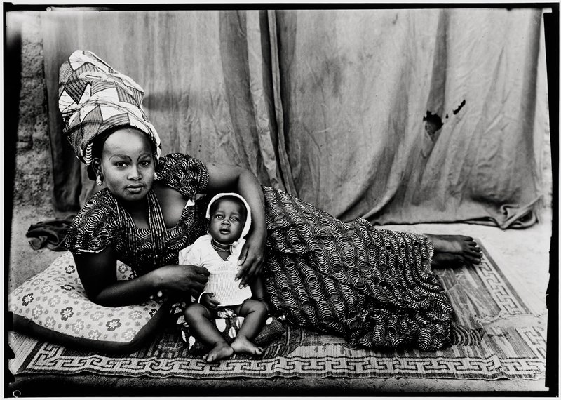 "woman lying on a rug with child seated on a pillow in front of her; she is wearing a turban, large earrings and a circular patterned dress. A young mother with her baby. She is wearing a taffeta headscarf, called a karton, because it is held up by a piece of cardboard. She also has a collection of gold rings called ""waterfalls"" (dyi suuru) on her right braid and a loose dress. . ."