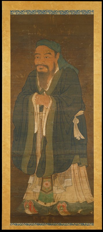 standing Confucius facing to his proper right, wearing a green coat; hands held together in front; long white fingernails; red shoes curl up from under edge of robe
