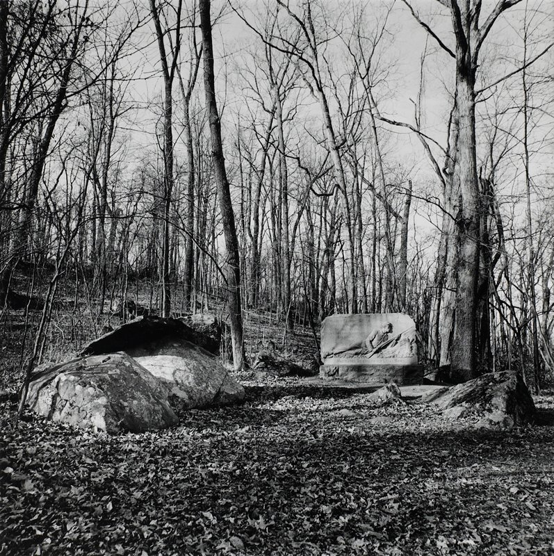 monument/relief sculpture of a reclining soldier with a rifle at R; large rocks in foreground; bare trees in background