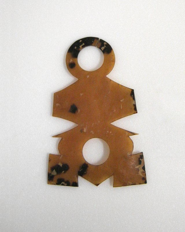 geometric shape with 2 circular cutouts; clear amber color with brown spots