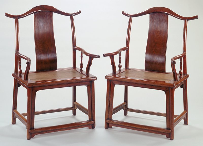 reddish brown wood chair with protruding crest rail and arms