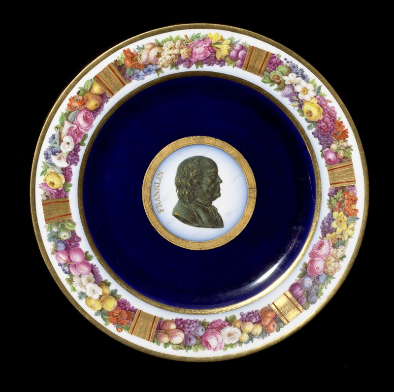 "plate with flowers and fruit at rim; blue ring surrounding green profile bust, with ""Franklin"" in gilt on L; gilt trim"