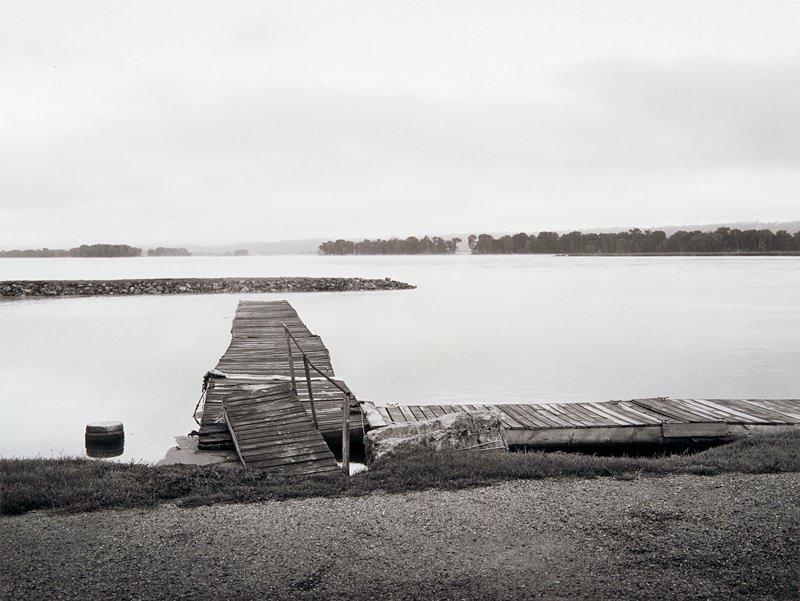 Old, broken-down docks; rocky sandbar extending toward center from left; trees visible on opposite shore