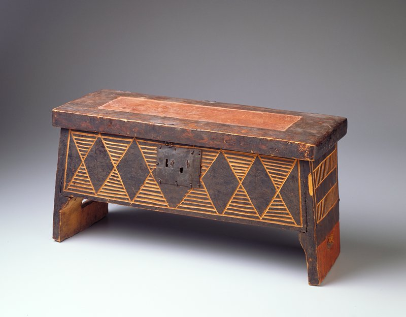 Rectangular box; sits on runners created by extended short sides; nonfunctional metal lock mechanism on front; hinged lid; decorated with incised diamonds and horizontal lines on front and incised bars with vertical stripes on sides; painted black and red