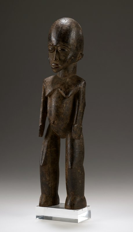 standing female figure with arms at sides; thick legs with undefined feet; spatula-like hands; long face with protruding chin; attached to plexi mount