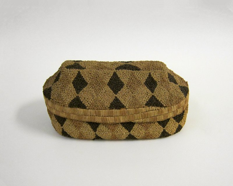 Oval-shaped basket with domed, slightly pointed cover; decorated with knots of fiber in an overall triangle and diamond pattern in dark, light and medium shades