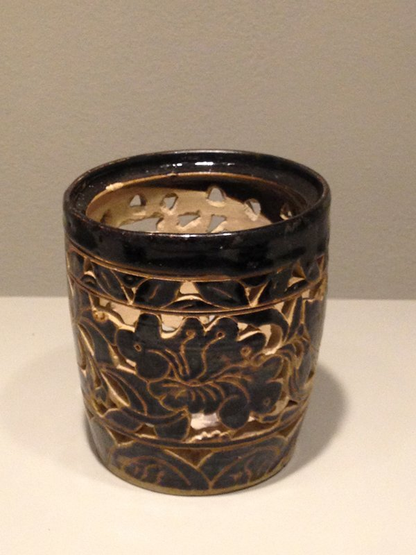 dark brown/black ceramic pot; open work carving in floral/foliage motif; inside bottom is decorated; incised lines on bottom
