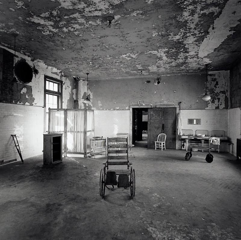 shabby room with worn hexagonal tile floor and peeling paint on walls and ceiling; 3 sinks in R corner; old medical equipment scattered throughout, including a crutch, a folding screen, stools, a wheelchair and a cart with a wash basin