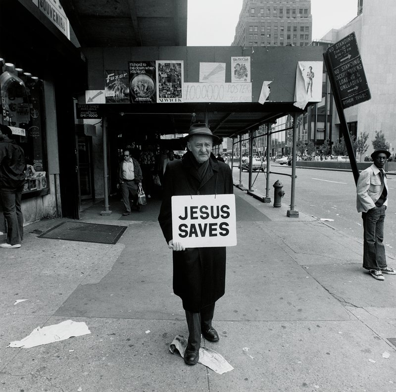 """old man wearing hat and overcoat, with a placard around his neck reading """"JESUS SAVES"""", walking down a city street"""