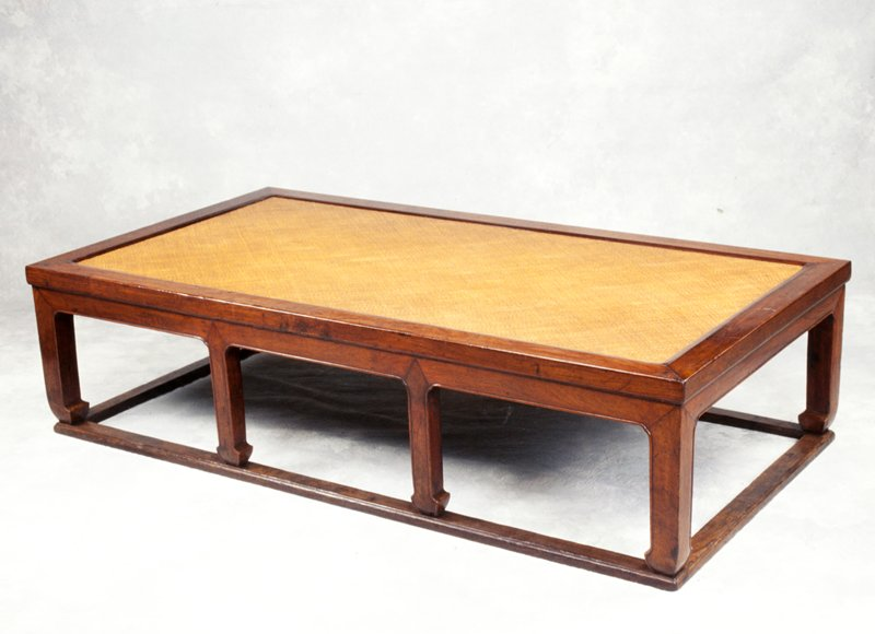 Low table with cane on top surface; four legs on each long side attached to runners on all four sides