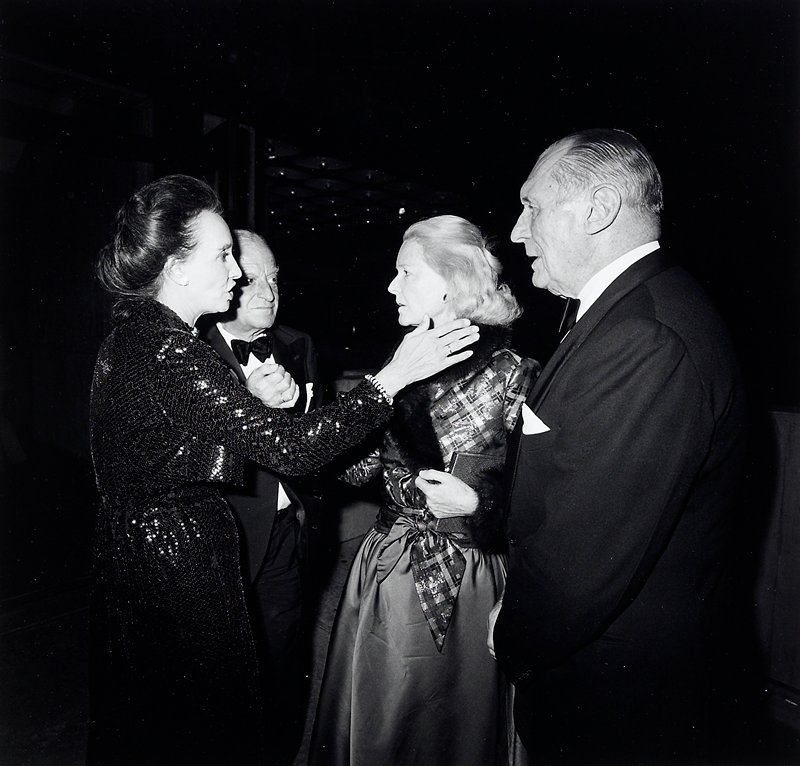 2 older couples; woman at L with updone hair, wearing sequined dress, with PR arm extended, standing in front of man in tuxedo; man at R in dark suit with woman, in shiny plaid bodice and silk skirt with fur stole, to his PR