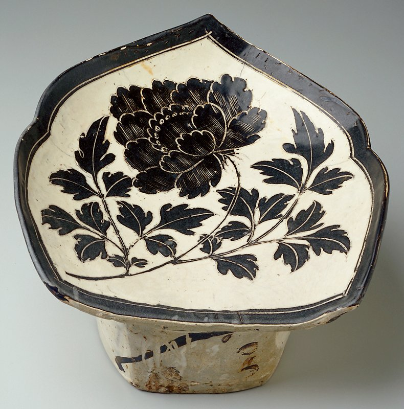 Top shaped like an abstracted leaf; top carved with a blooming peony in brown-black glaze; brown-black stripe around edge; cream ground