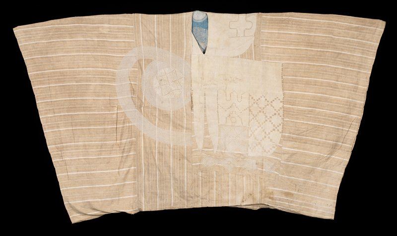 nubby tan fabric with white stripes; decorated with white, nearly solid embroidery at PL side, with curvalinear and circular designs at PR side and back
