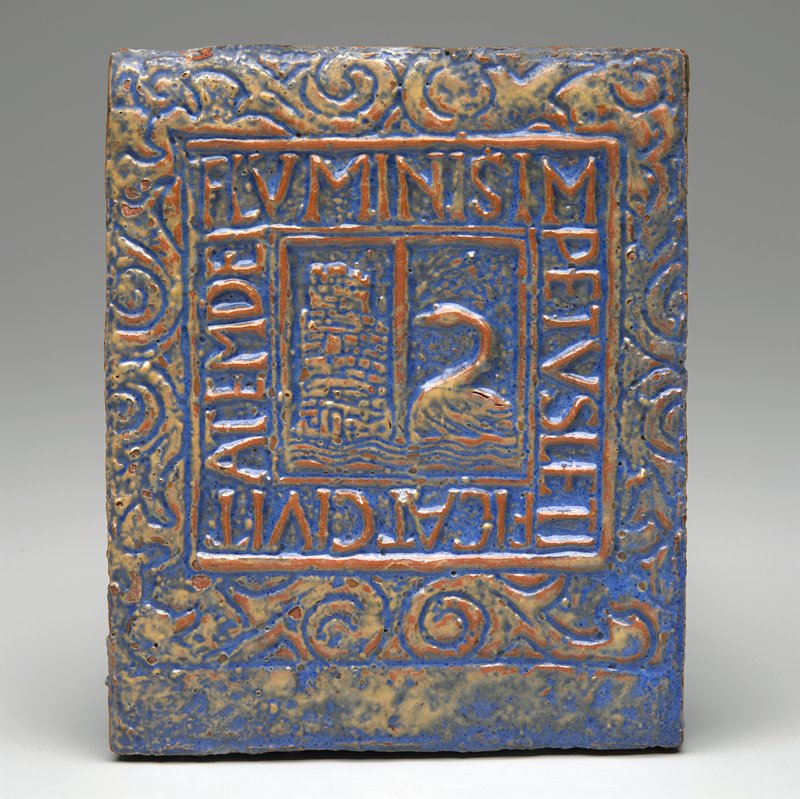 moulded decoration of tower and swan in center, surrounded by Latin Biblical inscription; blue, cream and rust glazes
