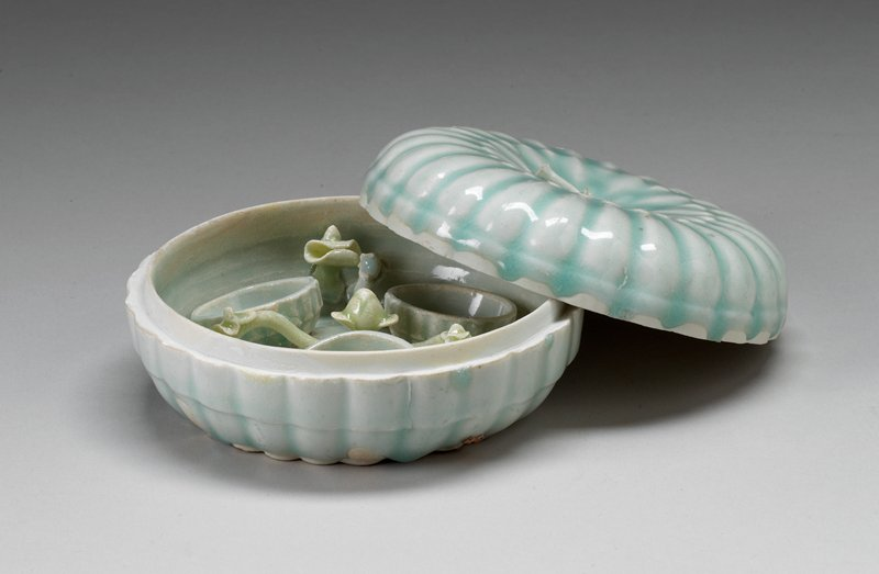 light blue glaze; slightly flattened melon form; interior has 3 small compartments divided by flowering branches