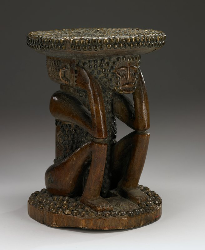 stool on a round base; seat supported by a female figure seated with the elbows resting on the drawn-up knees and the hands to the ears; face, torso, seat and base closely covered with numerous embedded brass tacks; soft patina
