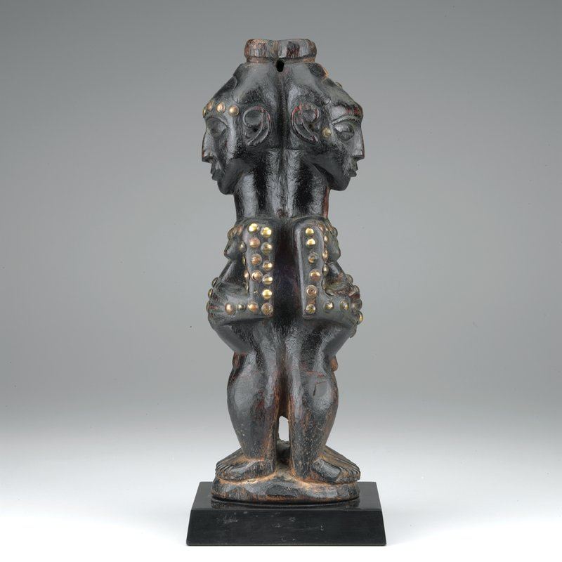 standing with legs apart on a round base; arms free of the body with the hands to the abdomens; identical faces with downcast eyes and slightly smiling expressions; embedded with numerous brass tacks; oily patina