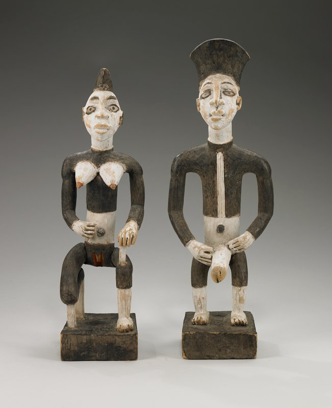 bi-colored black and white male figure with explicit sexual attributes; standing on square base; very light wood
