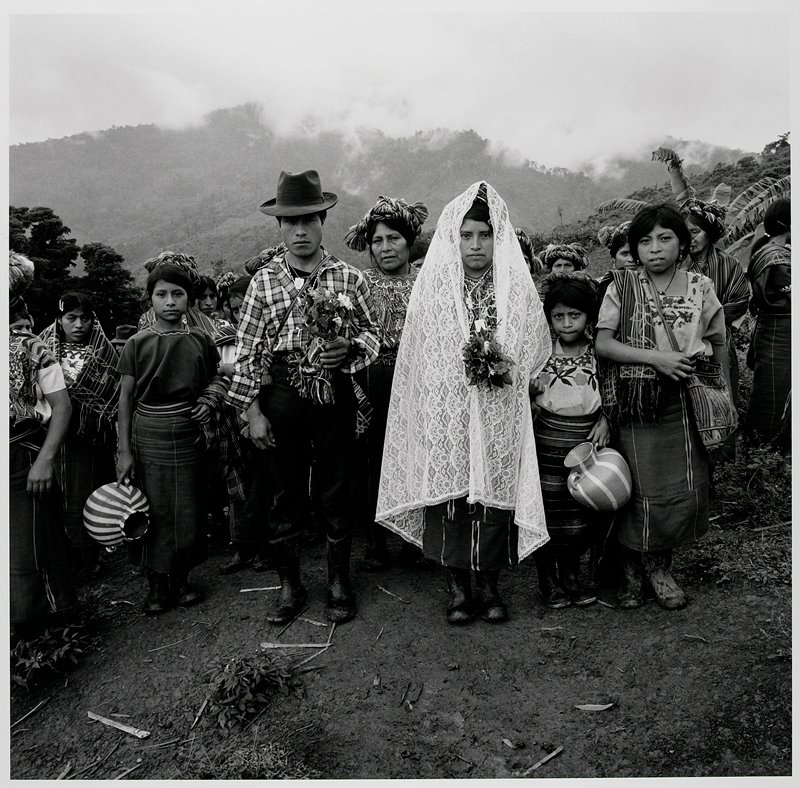 couple at center; woman at R wears a long lace veil and holds a small bouquet of flowers; man at L wears a fedora and plaid shirt and carries a small plant; women and girls at R and L and behind couple; all figures wear rubber boots