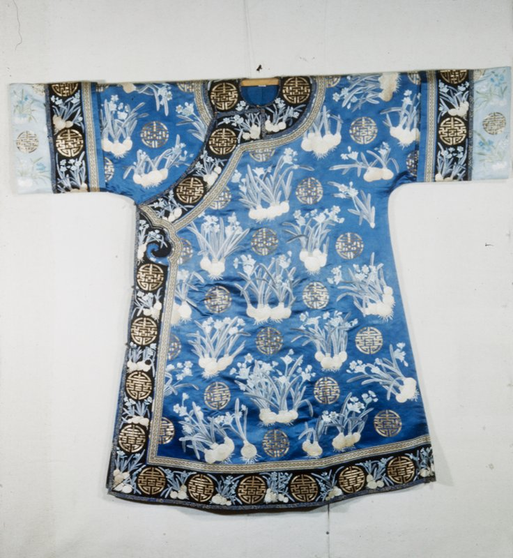 Empress robe of blue satin, attributed to Cixi, embroiderd with lily bulbs in shades of grey, pale blue-green and golden yellow. Happy Augury(?) signs alternate with lily bulbs over all. Wide border of black embroidered with same motifs around bottom, opening and cuffs of robe.
